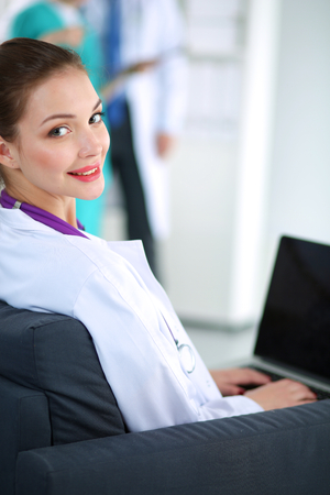 Beautiful young smiling female doctor sitting at the desk photo