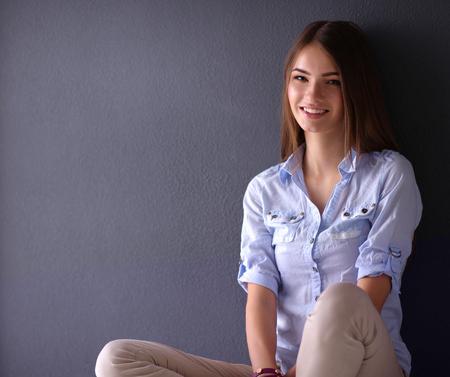 Joven mujer sentada en el suelo cerca de la pared oscura Foto de archivo