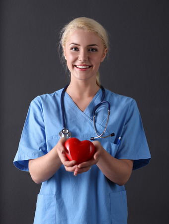 Doctor with stethoscope holding heart, isolated on gray background photo