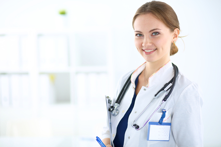 Woman doctor standing with folder at hospital Imagens