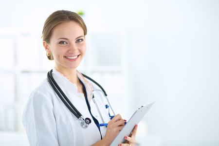 Woman doctor standing with folder at hospital Stock Photo