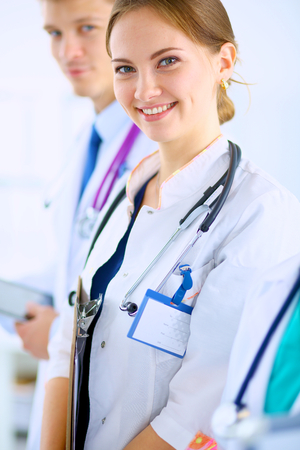 Attractive female doctor  with folder in front of medical group Stock Photo