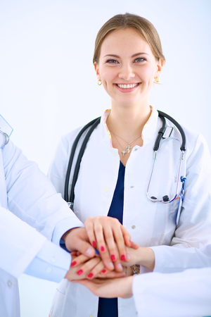 Doctors and nurses in a medical team stacking hands photo
