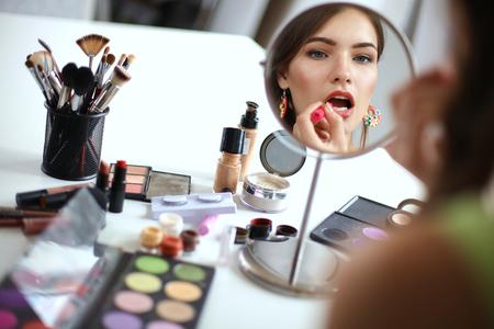 Jeune femme belle prise de maquillage près du miroir, assis à son bureau Banque d'images