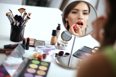 espejo: Mujer hermosa joven que hace maquillaje cerca del espejo, sentado en el escritorio