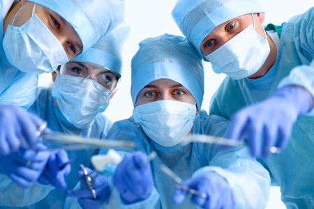 medical instruments: Below view of surgeons holding medical instruments in hands