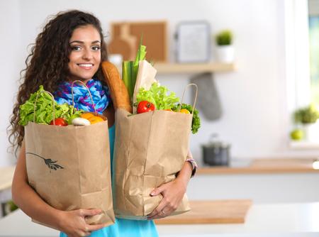 Jeune femme tenant épicerie sac avec des légumes .Standing dans la cuisine