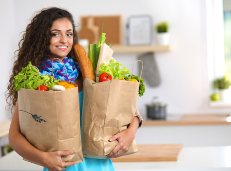 woman holding bag: Young woman holding grocery shopping bag with vegetables .Standing in the kitchen Stock Photo