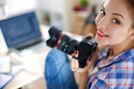 Female photographer sitting on the desk with laptop Stock Photo