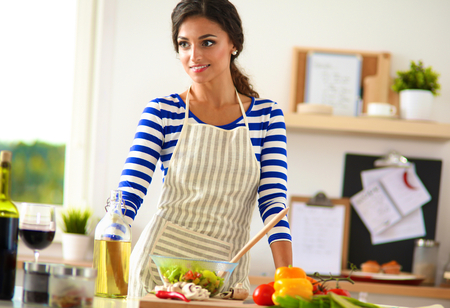 cook house: Young woman mixing fresh salad Stock Photo