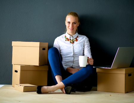 to unpack: Woman sitting on the floor near a boxes  with laptop