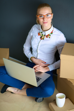 unpack: Woman sitting on the floor near a boxes  with laptop