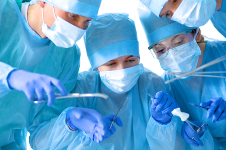 medicaid: Below view of surgeons holding medical instruments in hands