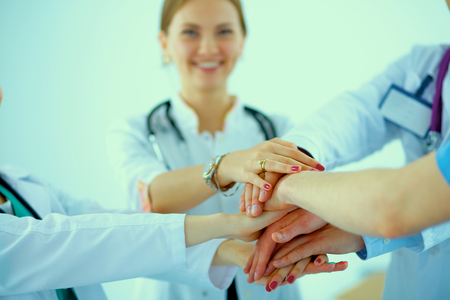collaborate: Doctors and nurses in a medical team stacking hands