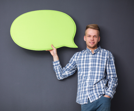 man holding sign: Man holding white blank speech bubble with space for text . Stock Photo