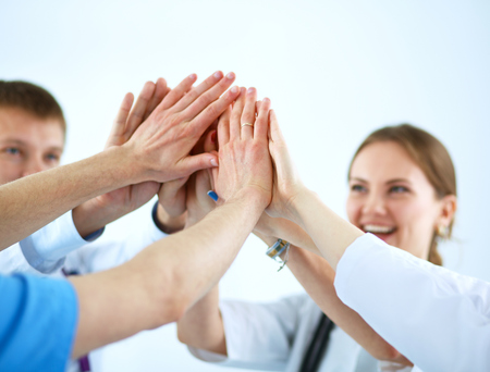 joining the team: Doctors and nurses in a medical team stacking hands  . Stock Photo