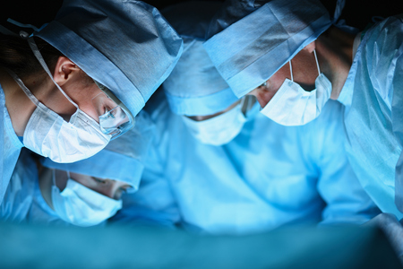 gloves nurse: Young surgery team in the operating room . Stock Photo