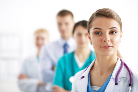 Attractive female doctor in front of medical group .