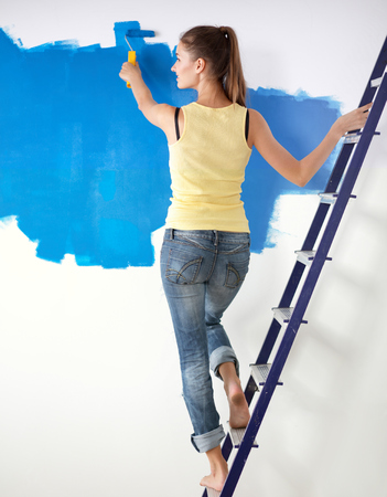 Beautiful young woman doing wall painting, standing near ladder Stock Photo