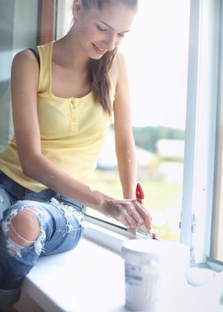 redecorating: Woman with a paintbrush carefully finishing off around a window frame