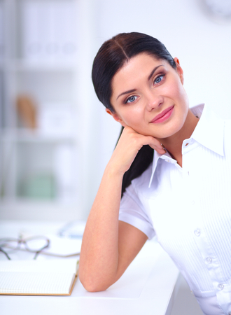gleeful: Attractive businesswoman sitting  in the office, isolated Stock Photo