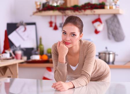 microondas: Mujer smilling joven que se coloca en su cocina. Foto de archivo