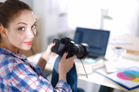 downloaded: Female photographer sitting on the desk with laptop.