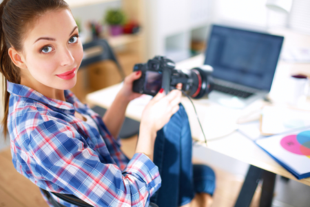 female photographer: Female photographer sitting on the desk with laptop.