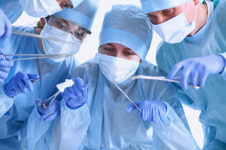 physicals: Below view of surgeons holding medical instruments in hands . Stock Photo