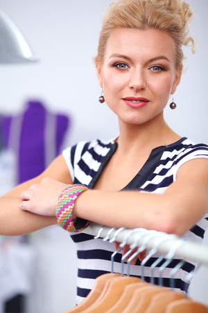 hangers: Beautiful young stylist near rack with hangers