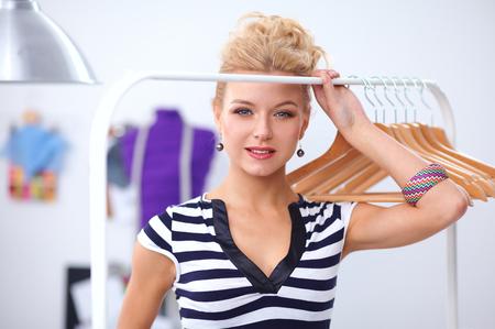 stylist: Beautiful young stylist near rack with hangers