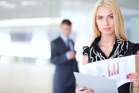 Femme d'affaires debout au premier plan avec un dossier dans ses mains.