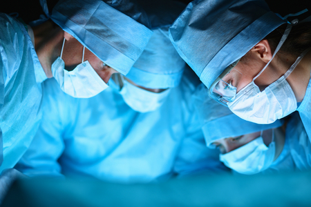surgical mask woman: Young surgery team in the operating room . Stock Photo