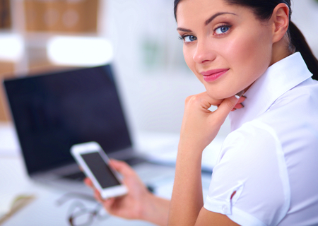 message sending: Businesswoman sending message with smartphone in office