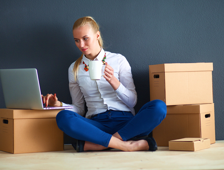 unpack: Woman sitting on the floor near a boxes  with laptop .