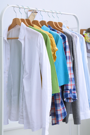 designer clothes: Clothes hang on a shelf in designer clothes store.