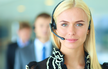 headset woman: Businesswoman with headset smiling at camera in call center. Businessmen in headsets on background Stock Photo