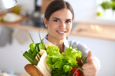 ok: Young woman holding grocery shopping bag with vegetables