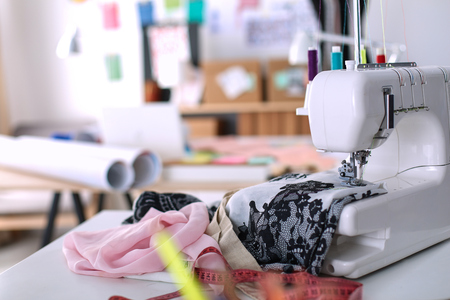 Designer work place with sewing machine, in office .