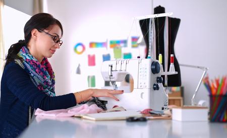 maquinas de coser: Mujer cosiendo joven mientras estaba sentado en su lugar de trabajo.