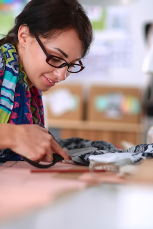 casual business: Fashion designer cutting textile next to a sewing machine . Stock Photo