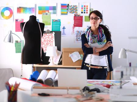 Vacker modedesigner står i studion.