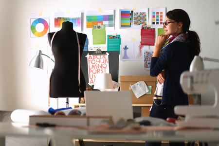 Beautiful fashion designer standing in studio . 스톡 콘텐츠