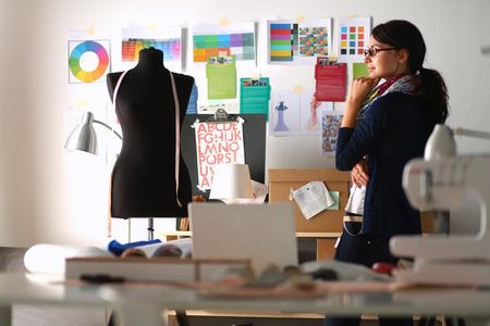 時尚: 美麗的時裝設計師站在工作室。 版權商用圖片