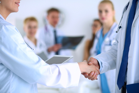 handshaking: Young medical people handshaking at office .