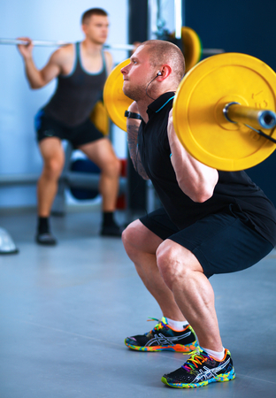 curls: Shot of a young man performing bicep curls in a gym Stock Photo