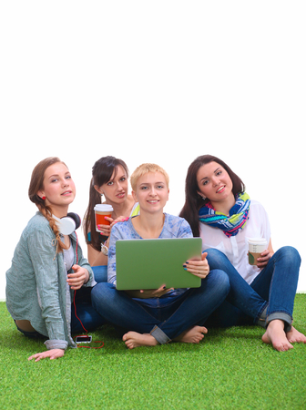buddies: Young women sitting on the grass using a laptop together Stock Photo