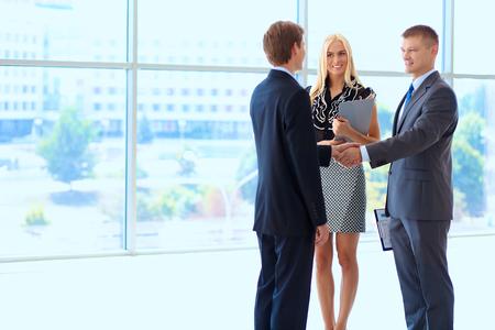 liderazgo empresarial: La gente de negocios dándose la mano después de reunirse.