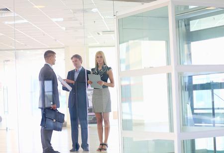 reunion de trabajo: Mujer de negocios de pie con su personal en segundo plano en la oficina moderna.