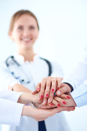 medical doctors: Doctors and nurses in a medical team stacking hands  . Stock Photo
